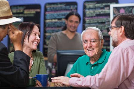 socializando: Riendo hombre mayor con un grupo de amigos en el restaurante