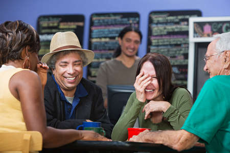 hysterical: Diverse group of adults joking in a coffee house Stock Photo