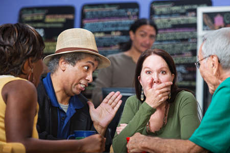 nosey: Embarrassed woman with hand on mouth with group in cafe Stock Photo