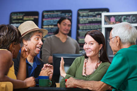 Woman gesturing man in cafe to stop talking photo