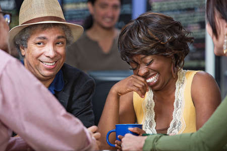 Diverse group of giggling men and women in coffee house photo