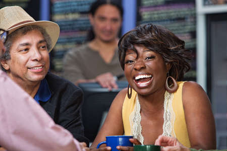 Diverse group of men and women laughing in restaurant photo
