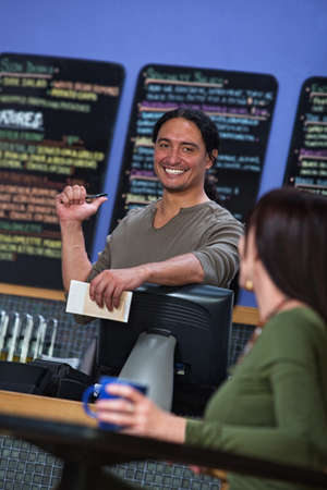 enthusiastic: Handsome cafe owner showing menu board to female customer