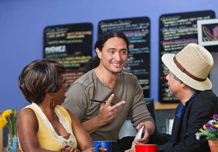 Handsome cafe owner with diverse customers taking orders photo