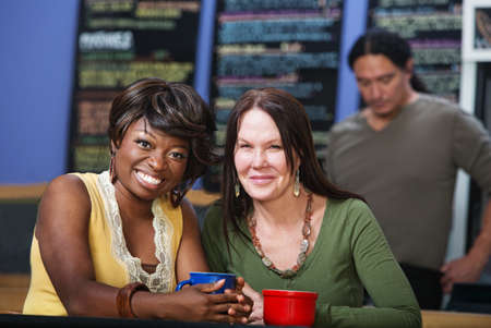 Diverse pair of adult friends smiling in restaurant photo