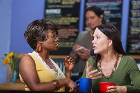 Pair of calm women in conversation at coffee house photo