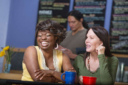 latina female: Diverse pair of women joking in coffee house Stock Photo