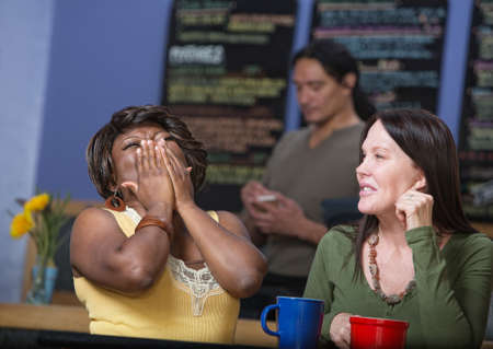 Laughing African woman with European woman in cafe photo
