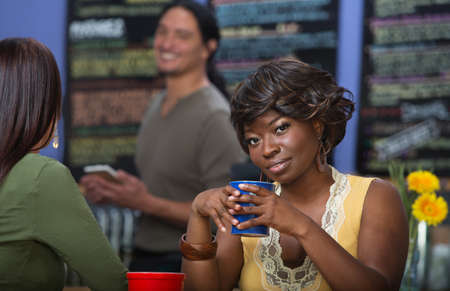 Grinning African woman with coffee mug in cafe photo