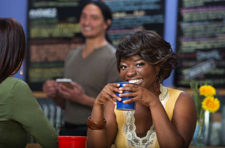 Pretty African woman with coffee mug in cafe photo