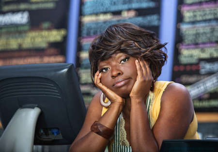 unhappy worker: Bored African woman with apron behind restaurant counter Stock Photo