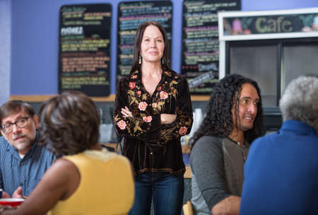 Cheerful woman standing in group of customers in cafe