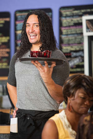 Happy Native American cafe owner serving drinks to customers