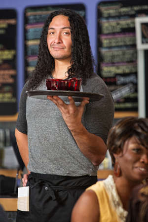 Male Hispanic cafe waiter serving drinks to customers