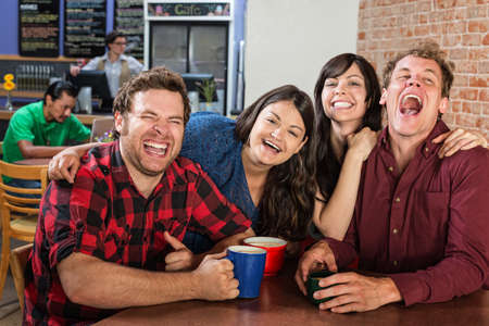 joking: Laughing group of cheerful friends in bistro