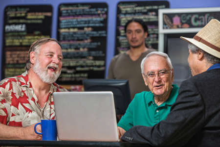Laughing people in a coffee house with laptop photo