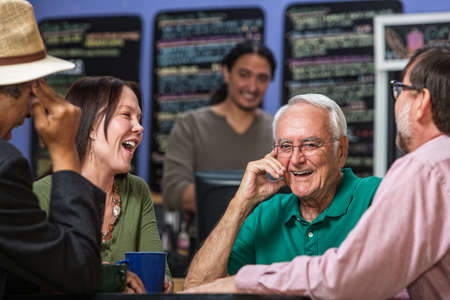 Mature people in a coffee house laughing Stockfoto