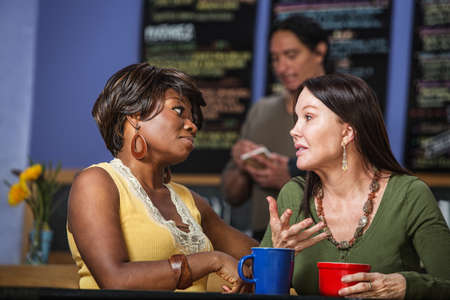 couple talking: African and European women in a coffee house talking Stock Photo