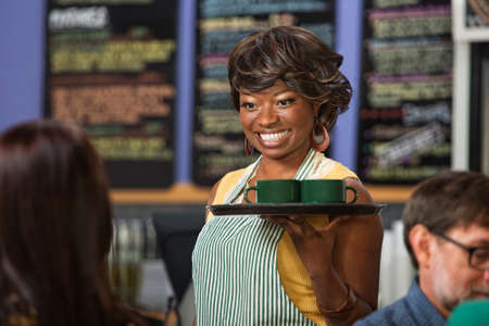 Beautiful Black woman in apron serving drinks on a tray photo