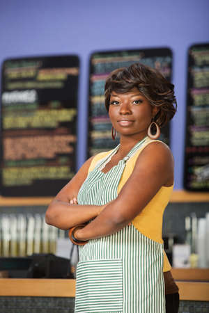 Confident Black woman in apron working in coffee house photo