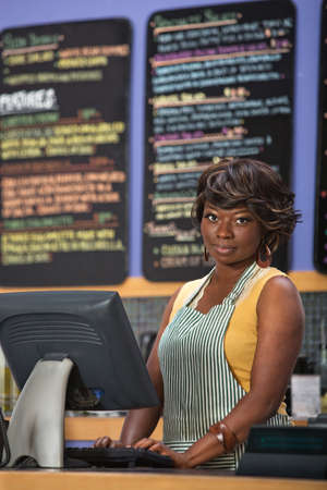 Beautiful cafe worker at cash register indoors photo
