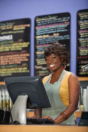 Gorgeous Black woman in apron working in coffee house photo