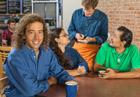 Grinning man with friends and barista at cafe Stock Photo