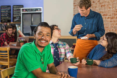 Grinning Asian man with friends and barista photo