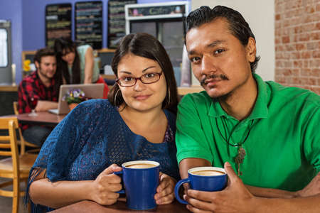 native american man: Grinning Latino and Asian couple in cafe