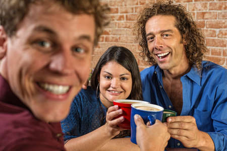 Excited friends toasting with coffee mugs in cafe photo