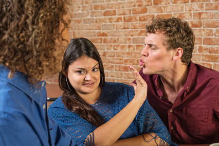 pervert: Annoyed woman being kissed by European male Stock Photo