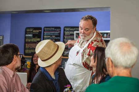 proprietor: Handsome cafe barista showing customers menu