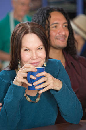 Cheerful mature woman in cafe with handsome male friend photo
