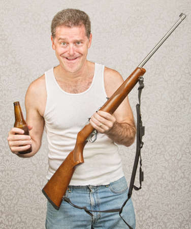 Single male hillbilly holding beer and rifle
