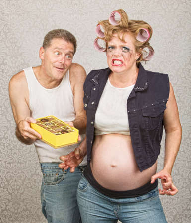 Angry pregnant woman in curlers with candy and man Stock Photo - 23050423