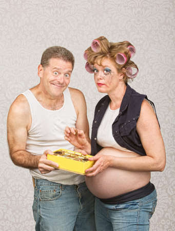smeared mascara: Guilty pregnant woman eating candy with smiling man Stock Photo