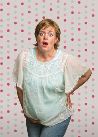 Startled pregnant woman on polka dot background photo