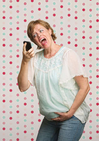 Pregnant woman holding belly while yelling at phone photo