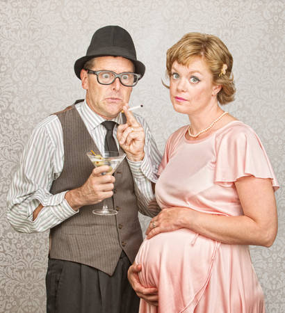 Worried man with martini and cigarette next to pregnant woman photo