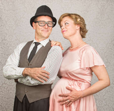Man with folded arms and happy pregnant female