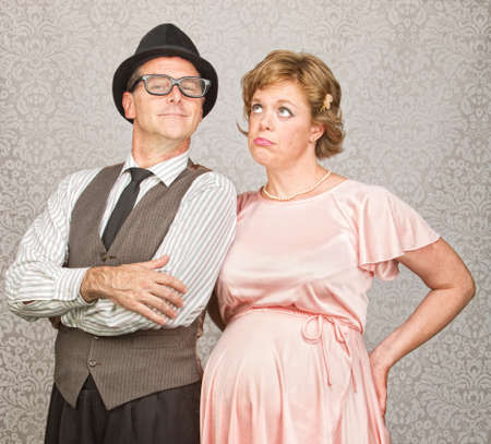 Proud 1950s man with bored pregnant woman