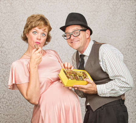 Businessman with gift of chocolate for pregnant woman photo