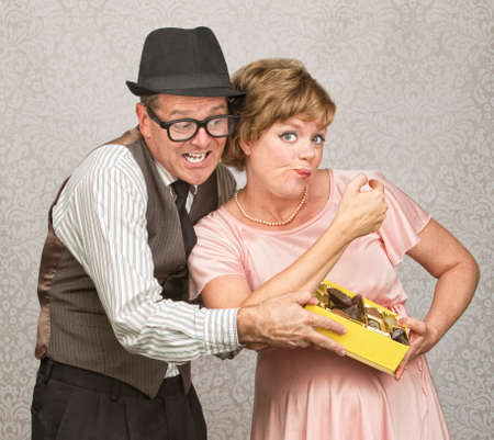 egoista: Mujer embarazada Selfish escondiendo caramelos de marido Foto de archivo
