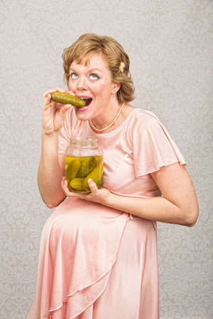 guilty pleasure: Overjoyed pregnant female eating from a jar of pickles
