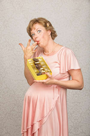 guilty pleasures: Single pregnant woman with candy licking her fingers Stock Photo