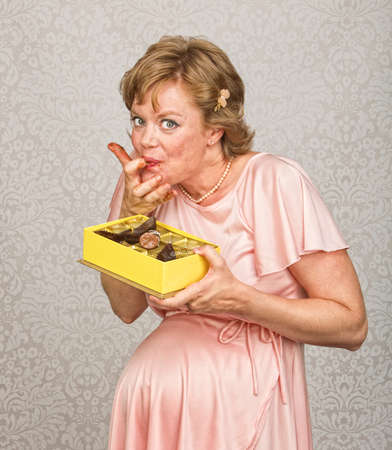 finger licking: Happy expecting woman holding chocolates and licking fingers Stock Photo