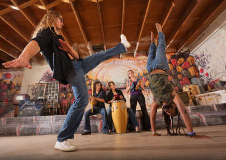 Capoeira artist kicking towards man in handstand during performance photo