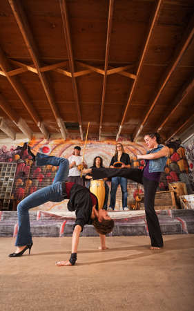Pair of female of capoeira performers sparring together photo