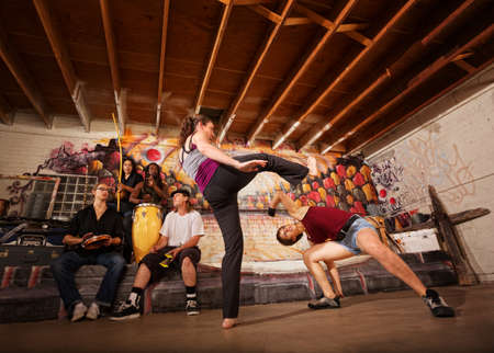 Woman dodging a capoeira front kick indoors