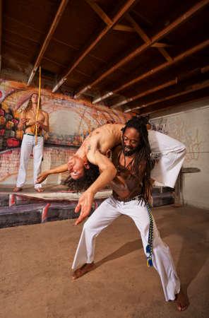 over shoulders: Capoeira performer holding partner in back bending over shoulders